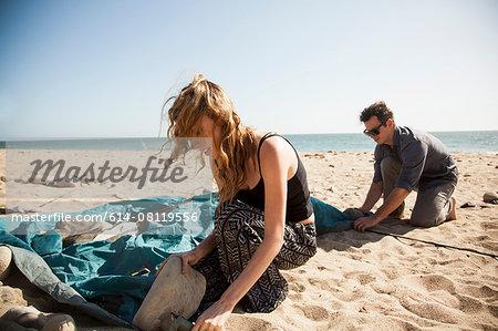 Couple setting up tent on beach, Malibu, California, USA