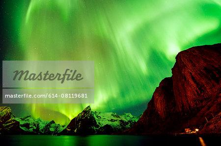 View of green aurora borealis over sea and mountains, Reine, Norway