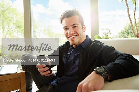 Portrait of smiling man sitting on floor holding smartphone