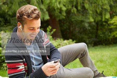 Portrait of man laying in garden listening to smartphone wearing earphones
