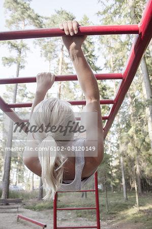Girl hanging on monkey bars
