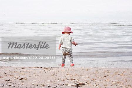 Baby girl standing on beach