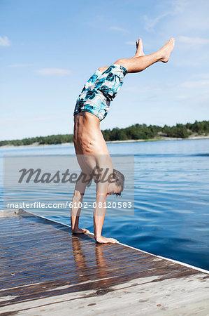 Teenage boy doing handstand on jetty