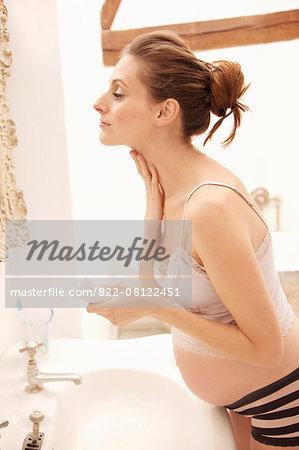 Pregnant Woman Applying Beauty Cream on Neck