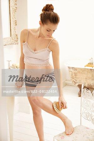 Pregnant Woman Exfoliating her Leg in Bathroom
