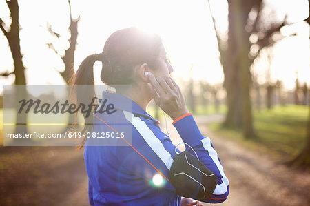 Mature female runner in park adjusting earphones