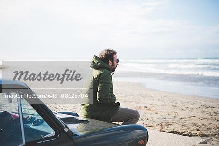 Mid adult man sitting on vintage car on beach, Sorso, Sassari, Sardinia, Italy