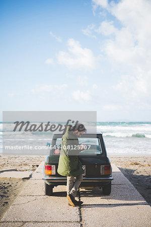 Man with vintage car parked on beach reading smartphone texts, Sorso, Sassari, Sardinia, Italy