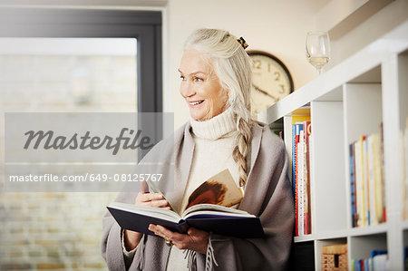 Senior woman reading book at home