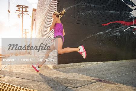 Female runner running along sidewalk