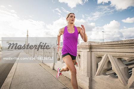 Young female runner running across bridge, Los Angeles, California, USA