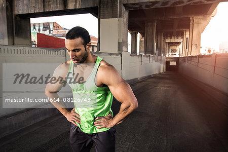 Muscular male runner taking a break under city bridge