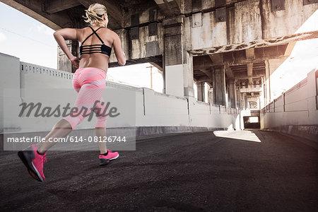 Female runner running under city bridge
