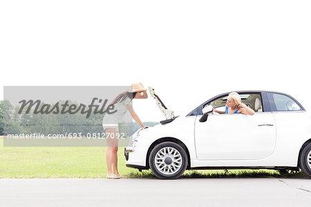 Woman looking at female friend repairing broken down car on country road
