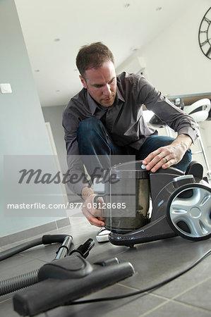 France, man using  vacuum cleaner.