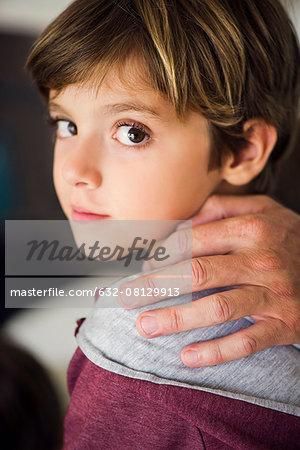 Parent's hand on boy's shoulder, cropped