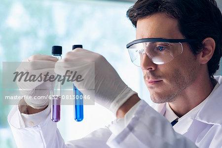 Scientist scrutinizing test tubes in lab