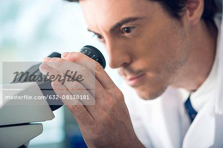 Scientist analyzing specimen under microscope