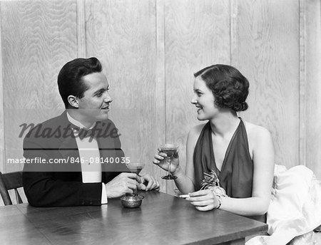 1930s 1940s COUPLE DRINKING TOASTING CLUB TABLE SMOKING CIGARETTE MAN WOMAN MEN WOMEN COUPLES TUXEDO MARTINI RESTAURANT PARTY