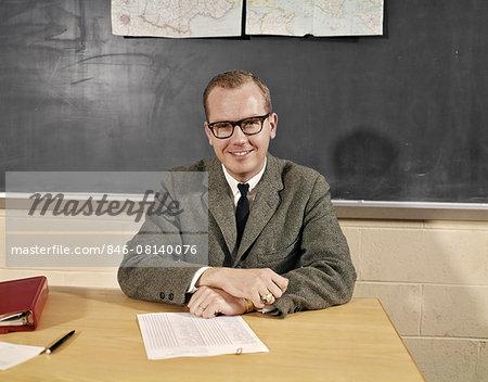 1960s SMILING MALE SCHOOL TEACHER SITTING AT DESK WEARING EYEGLASSES LOOKING AT CAMERA