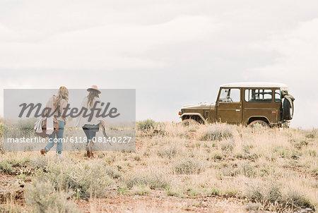 Two women walking towards a 4x4 parked in a desert.
