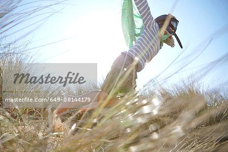 Young boy on beach, wearing fancy dress, pretending to fly