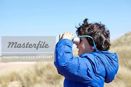 Young boy on beach, looking through pretend binoculars