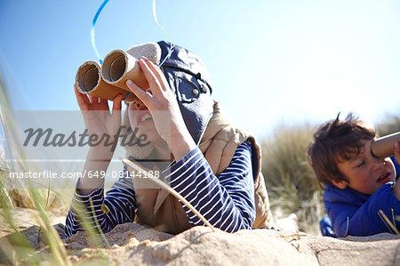 Two young boys on beach, looking through pretend binoculars