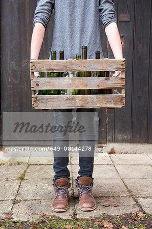 Teenage boy carrying empty bottles in wooden crate