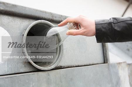 Person recycling milk bottle in bottle bank