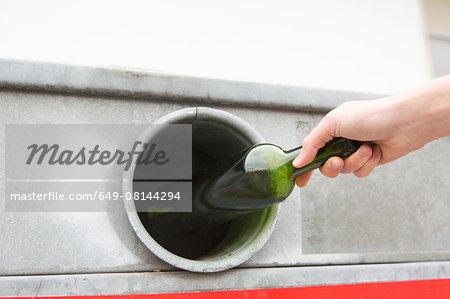 Person recycling wine bottle in bottle bank