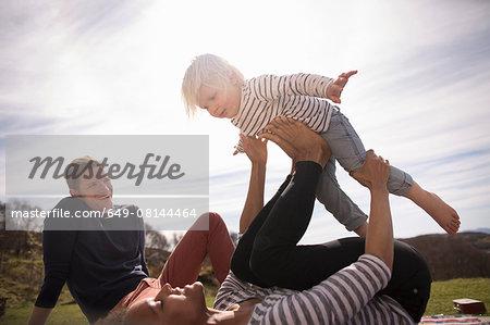 Mother balancing son on feet