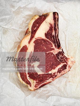 Raw beef steak on paper
