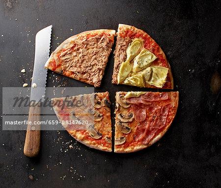 A pizza with tuna, mushrooms, Parma ham and artichokes, sliced