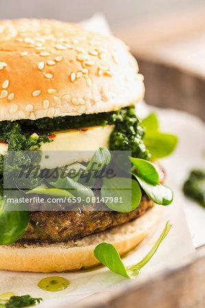 A vegetarian burger with a bean patty, chimi-churri, halloumi and lamb's lettuce