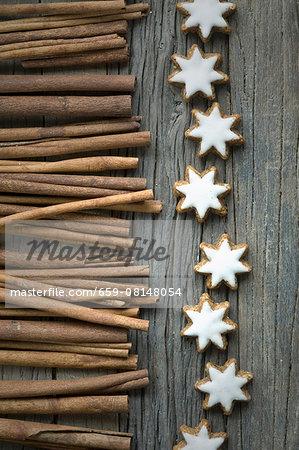 Cinnamon sticks and cinnamon stars on a wooden surface