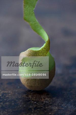 A kiwi, partially peeled