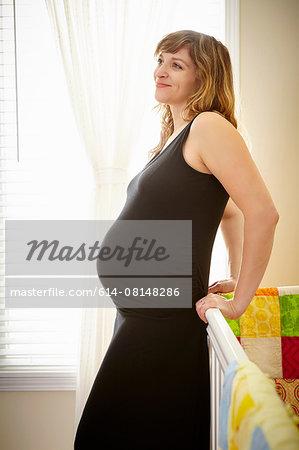 Pregnant woman leaning against crib in nursery