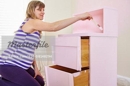 Pregnant woman painting nursery dresser pink
