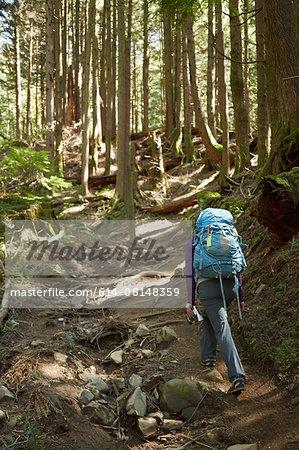 Female backpacker hiking in woods