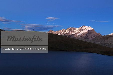 Hiker admires sunset on Rossett Lake at an altitude of 2709 meters, Gran Paradiso National Park, Alpi Graie (Graian Alps), Italy, Europe