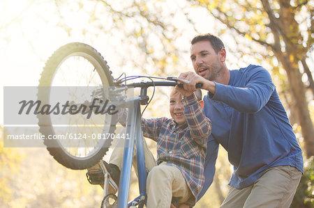 Father teaching son wheelie on bicycle