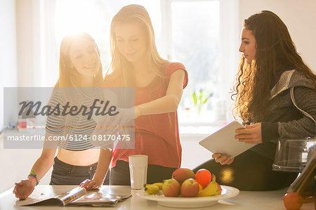 Teenage girls taking selfie with camera phone in kitchen