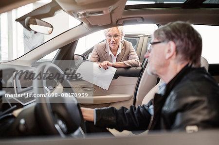 Senior saleswoman explaining features to man sitting in car at shop