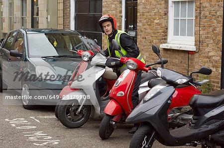 Motor scooter rider parking on street