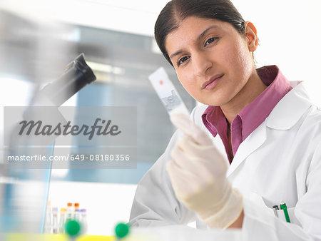 Female scientist in lab testing blood sample using microscope