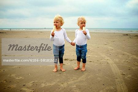 Twins eating icecream on the beach