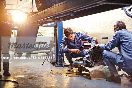 Mechanics examining part in auto repair shop