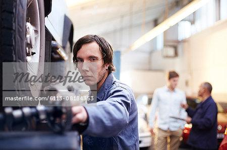 Mechanic reaching for part in auto repair shop