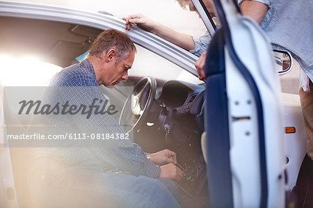 Mechanic working inside car in auto repair shop